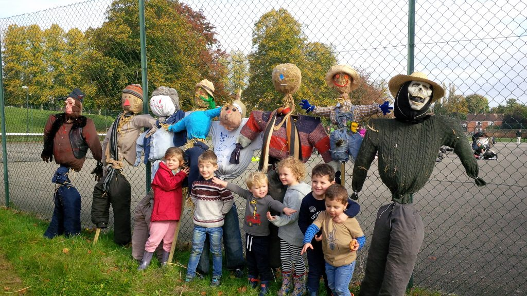 Scarecrow making event October 2016. Scarecrows and owners lined up by the tennis court fence.